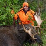 Man posing with a bull moose