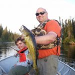Father and son posing with a walleye fish