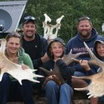 Family posing with bull mooose rack