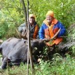 2 men posing with a bull moose