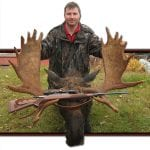 Man posing with his bull moose trophy