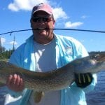 Man holding a pike with a fishing rod in his mouth