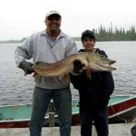 Father and son holding a pike
