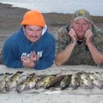 2 friends posing with huge haul of walleye