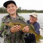 Father and son posing with a walleye catch