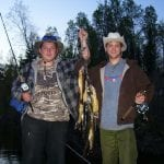 2 friends posing with as huge haul of walleye fish